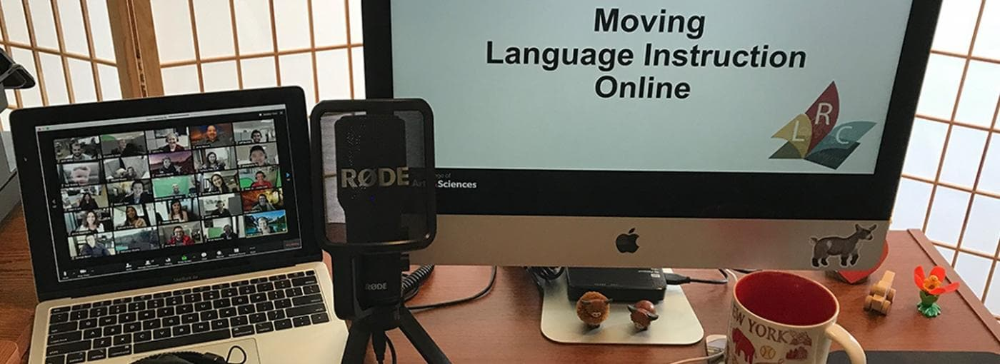 A language learner's desk, containing two computers running Google Slides and Zoom, a microphone, and a cup of coffee